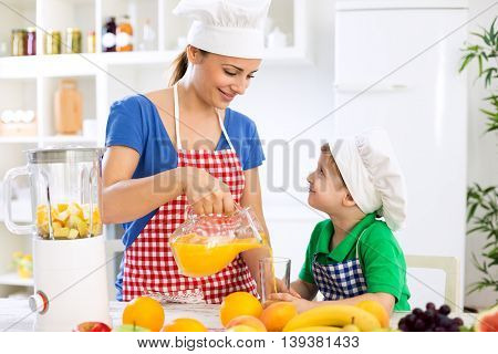 Beautiful Happy Mother Pour Orange Juice To Her Child Boy