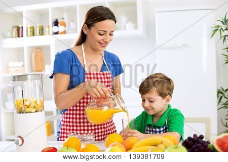 Young Mother And Child Prepare Fruits Juice