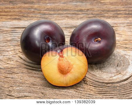 ripe black plums on wooden background in studio