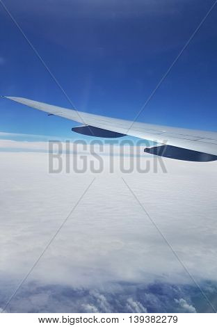 Wing of plane on beautiful blue sky and clouds view from window of the airplane