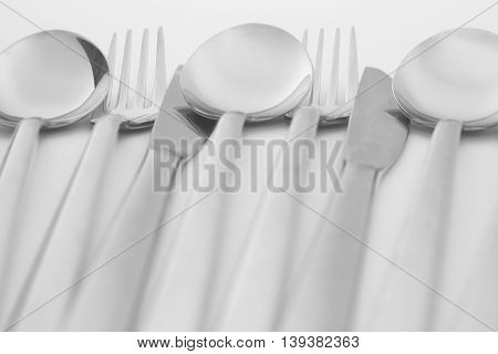 Spoons forks and knifes are on white background.