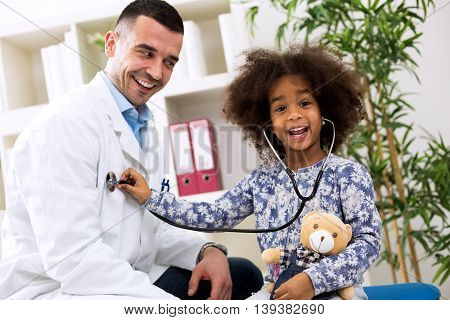 Smiling African Girl Playing With Pediatrician