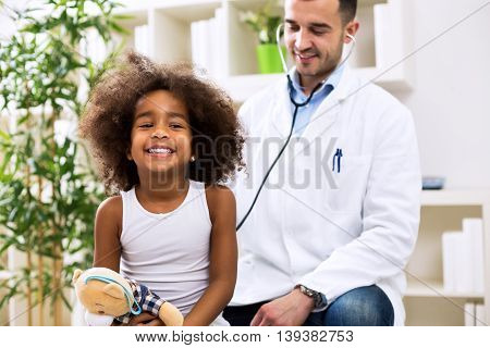 Doctor Pediatrician Examining Cute Smiling African Girl