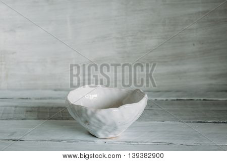 white clay bowl bowl of handmade clay white bowl on a light background.