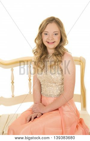 A woman with down syndrome sitting on a bench in her vintage dress with a smile.