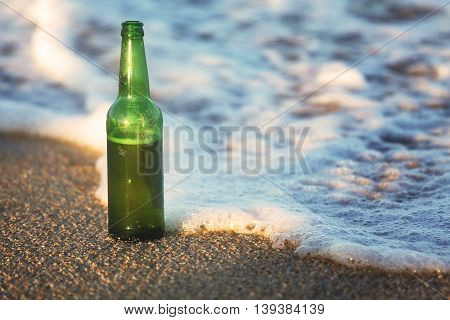 A bottle of beer on the beach. Waves wash a beer bottle.