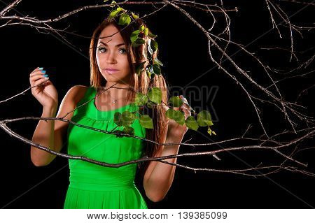 Woman In A Green Dress Between Dry Branches