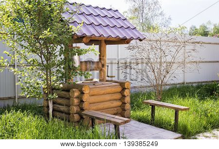 Beautiful well-maintained wooden well with a bucket.