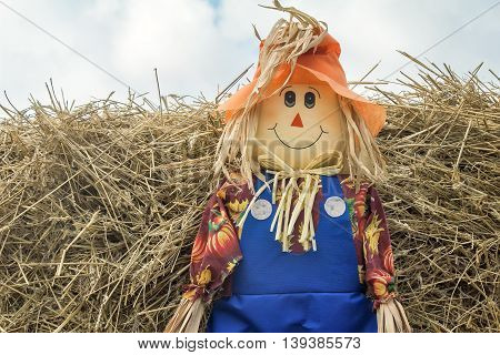 Funny doll of rags in the sight of the little man in the hat on the background of straw stacks.