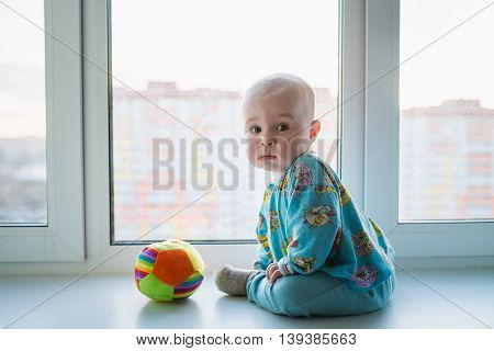 Little baby boy lonely sitting near the window.