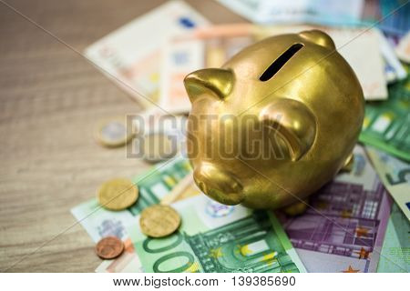 Piggy Bank With Euro On Wooden Table