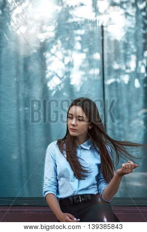 Beautiful girl standing near a window. The reflection in the window.