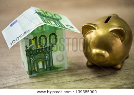 Piggy Bank And House Built Of 100 Euro Banknotes