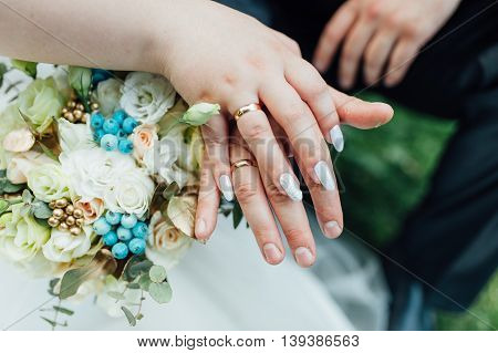 Hands and rings on wedding bouquet close up.