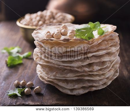 Tower thin crispy loaves of useful home cakes with chick-pea flour for home vegetarinskogo and healthy eating. On a dark wooden background with sprigs of coriander and chickpeas dry. selective focus