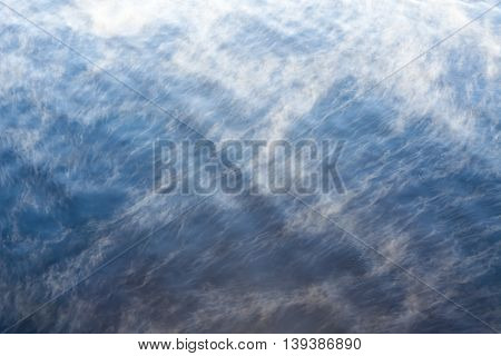 Water vapor on surface of cold icy water at sunny cold winter day