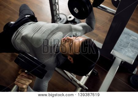 Man during bench press exercise at gym club, healthcare concept