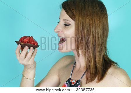 woman eating a strawberry tartlet over a blue background