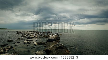 Seascape of stone beach with a dramatic cloudy sky. Beautiful view at the coast of the Black Sea in Balchik city Bulgaria.