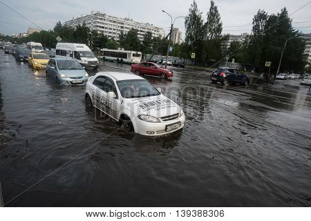 Saint-Petersburg Russia - June 16 2016: A number of cars on city road. Water on the road on a rainy day.