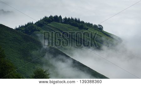 Detailed view of green mountains over the clouds