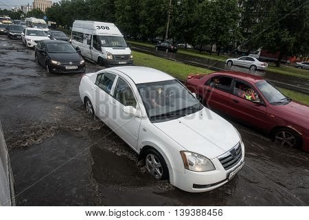 Saint-Petersburg Russia - June 16 2016: Cars in traffic on city road. The road is filled with water after a rain shower.