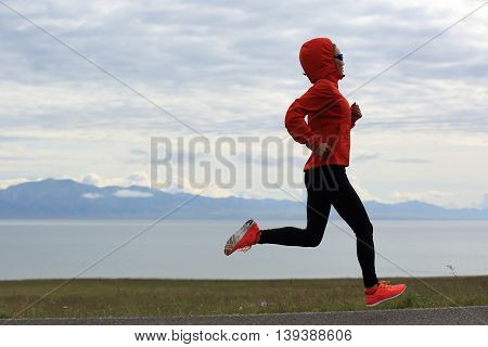young fitness woman runner running on seaside trail