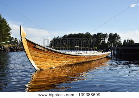 Long rowing boat laying in the water with blue sky in background picture from Sweden.