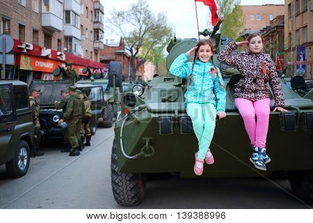 SAMARA - MAY, 6, 2015: Two girls (with model releases) pose on armored vehicle in Samara during military celebration. Red Square is not affected by military equipment on parade May 9th