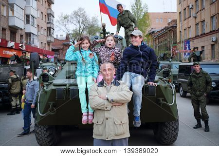 SAMARA - MAY, 6, 2015: Boy, man and two girls (with model releases) pose on armored vehicle in Samara during military celebration. Red Square is not affected by military equipment on parade May 9th
