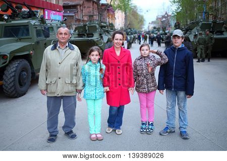 SAMARA - MAY, 6, 2015: Boy, man, woman and two girls (with model releases) pose near armored vehicles during military celebration. Red Square is not affected by military equipment on parade May 9th