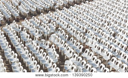many white plastic chairs are arranged in rows on gray pavement in the auditorium in the street