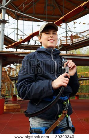 Smiling boy holds safety rope near Rope way on special playground