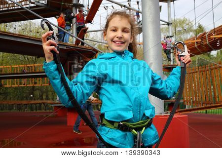 Smiling pretty girl holds safety rope near Rope way on special playground