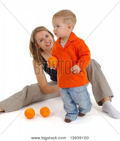 Little boy with beautiful mom on white background looking at orange fruits