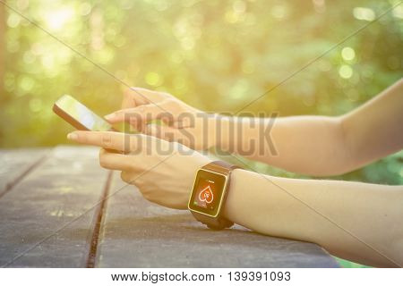 Close up of female hands using smart phone and wearing smart watch with heart rate app displayed at the desk in the park. New technologies and lifestyle concepts.