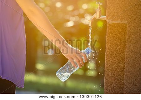 Close up of female hand pouring drinking water in plastic bottle on faucet in the park. Nature, summer. technology and healthy lifestyle concepts.