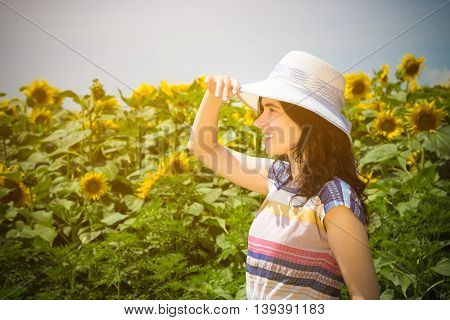 Side view portrait of young female wearing hat in the sunflower field during the summer day. Summer season, retro and fashion concepts.