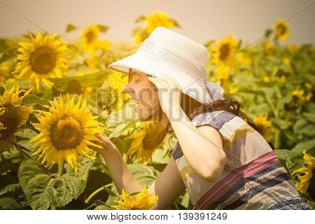 Side view of young female wearing hat in the sunflower field during the summer day. Summer season, retro and fashion concepts.