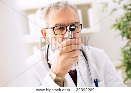 Otolaryngologist specialist looking through otoscope, close up
