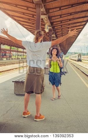 Man meeting his girlfriend from her trip at the train station