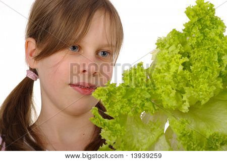 Young girl with mouth full of lettuce