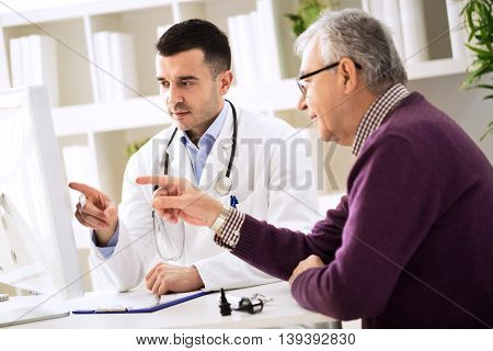 Doctor And Patient Pointing On Computer