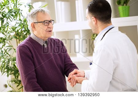 Young Doctor Holding Hand Talking And Relaxing Old Patient