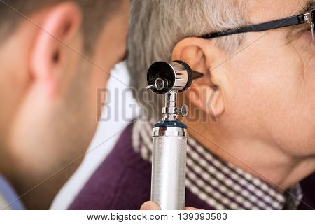 Doctor Examining old Patient's Ear, close up
