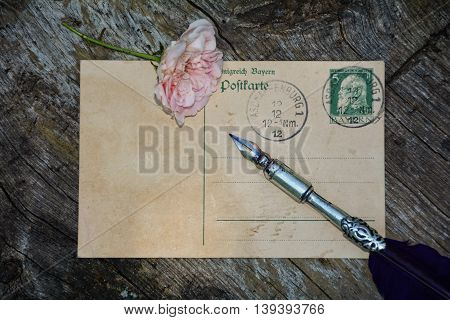 old blank vintage postcard with old stamp is on old wood with pink rose and nib