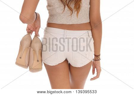 A closeup image of a slim young woman in shorts from the back holding her heels isolated for white background.