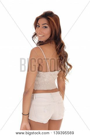 A gorgeous woman standing from the back looking over her shoulder in beige shorts isolated for white background.