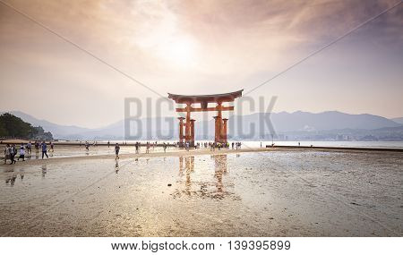 MIYAJIMA, JAPAN - MAY 27: Tourists walk around the famous floating torii gate of the Itsukushima Shrine on Miyajima at sunset on May 27,2016 in Miyajima, Japan