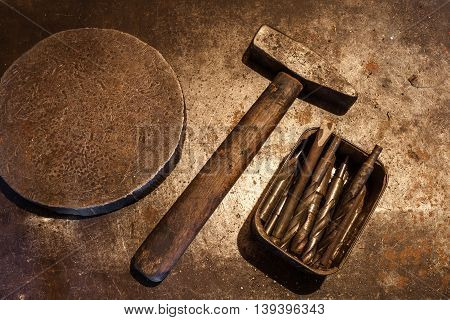 The old steel hammer with wooden handle iron heavy ring and drill bits for metal in the box on the metal background